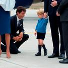 Canadian Prime Minister Justin Trudeau (C) kneels to talk to Prince George as his father Prince William, The Duke of Cambridge, speaks with the Governor General David Johnston (R) and Catherine, The Duchess of Cambridge (C) holds their daughter Princess Charlotte