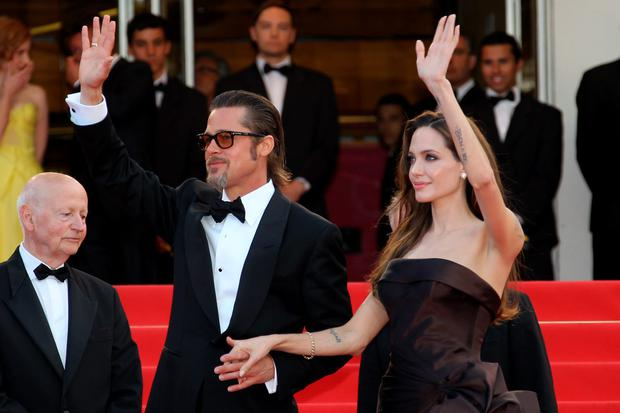 US actor Brad Pitt and his wife, US actress Angelina Jolie, wave on the red carpet before the screening of