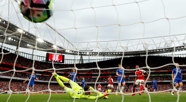 Theo Walcott finds the net for Arsenal's second goal despite the efforts of Chelsea goalkeeper Thibaut Courtois. Photo: Reuters