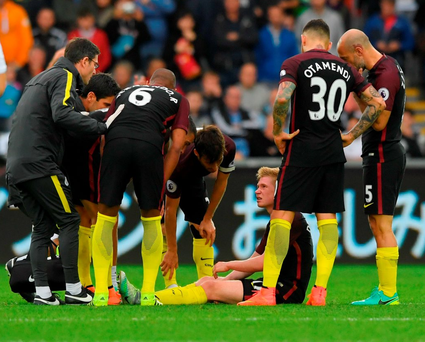 Injured Kevin De Bruyne speaks with Manchester City's physios. Photo: Getty