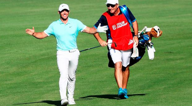 Rory McIlroy celebrates alongside his caddie J.P. Fitzgerald after holing a shot for eagle on the 16th hole