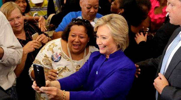 Democratic presidential candidate Hillary Clinton takes a selfie as she meets with attendees during a campaign stop at the Frontline Outreach Centre in Orlando Credit: AP