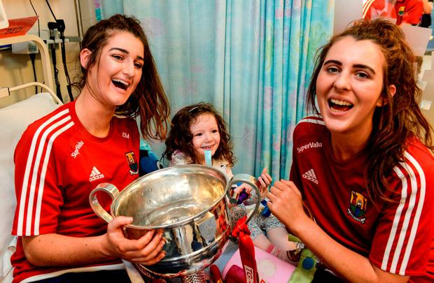 Cork players Eimear Meaney and Maeve O'Sullivan met Áine McInerney (4), from Kells, Co Meath, when the victorious ladies football team visited Temple Street Children's Hospital with the Brendan Martin Cup. Photo: Piaras Ó Mídheach/Sportsfile