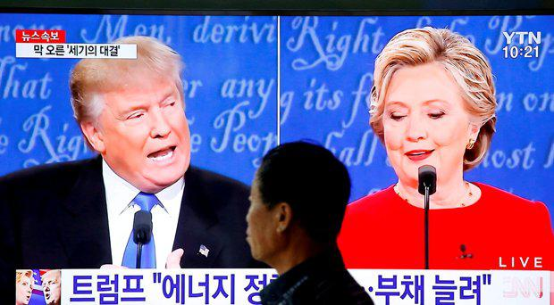 A man walks past a TV broadcast of the first presidential debate between U.S. Democratic presidential candidate Hillary Clinton and Republican presidential nominee Donald Trump, in Seoul, South Korea, September 27, 2016