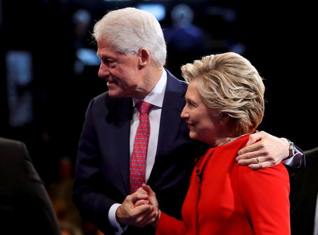 Democratic U.S. presidential nominee Hillary Clinton holds hands with her husband, former President Bill Clinton, as they leave the stage after the conclusion of the first debate with Republican U.S. presidential nominee Donald Trump at Hofstra University in Hempstead, New York, U.S., September 26, 2016. REUTERS/Joe Raedle/Pool