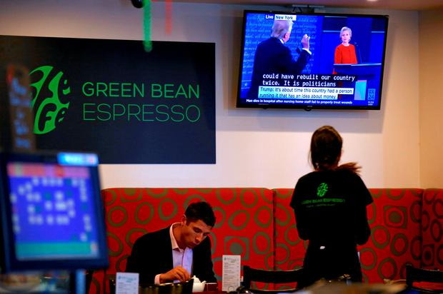 A customer and waitress can be seen in a cafe in Sydney, Australia, September 27, 2016 as Republican U.S. presidential nominee Donald Trump and Democratic U.S. presidential nominee Hillary Clinton are displayed on a screen during the first presidential debate. REUTERS/David Gray