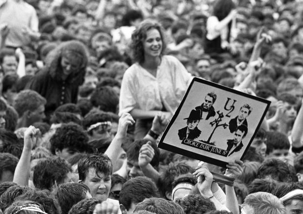 U2 - The Joshua Tree Tour, 2nd leg: Europe. Croke Park, Dublin, June 1987... View of the many fans in the audience. One holds up a poster/placard of the band. (Part of the Independent Ireland Newspapers/NLI Colection)
