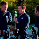 Rory McIlroy of Northern Ireland (C) shows his putter to European team Vice-Captain Ian Poulter (L) and Andy Sullivan of Great Britain during team photos at Hazeltine National Golf Course in Chaska, Minnesota