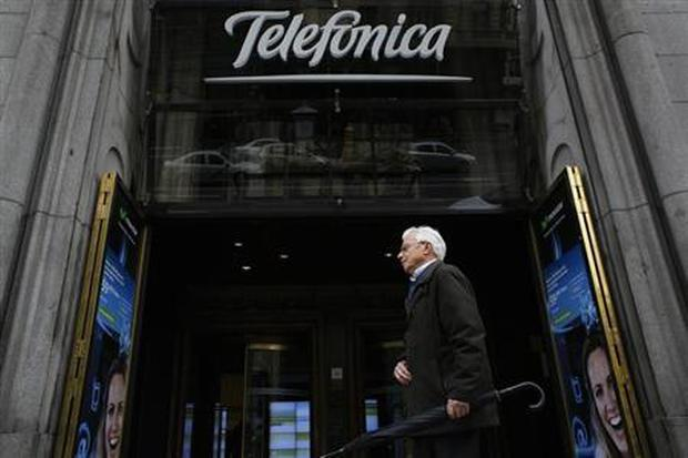 A man walks past Telefonica's building in central Madrid
