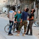 People look at the sky fearing an airstrike in the rebel-held al-Myassar neighbourhood of Aleppo, Syria