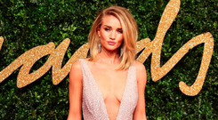 British model Rosie Huntington-Whiteley poses for pictures on the red carpet upon arrival to attend the British Fashion Awards