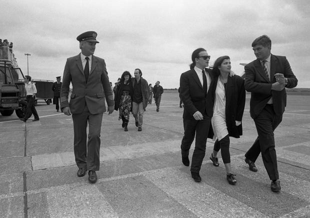 8/8/1987 Bono and his wife Ali Hewson arriving at Cork Airport prior to the U2 Joshua Tree Tour concert in Páirc Uí Chaoimh.. Behind them are The Edge (David Dave Evans) with arm around lady and further behind, Adam Clayton. (Part of the Independent Ireland Newspapers/NLI Colection)