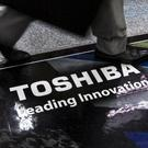 A man walks past a logo of Toshiba Corp at an electronics store in Tokyo. REUTERS/Thomas Peter