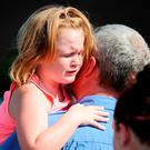 Lilly Chapman, 8, cries after being reunited with her father, John Chapman at Oakdale Baptist Church on Wednesday, Sept. 28, 2016, in Townville, S.C. (AP Photo/Rainier Ehrhardt)