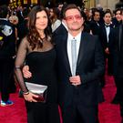 Bono (C) of the rock band U2 and wife Ali Hewsonon arrive on the red carpet at the 86th Academy Awards in 2014