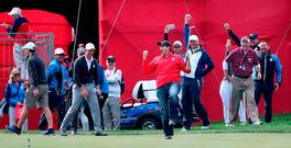 A spectator celebrates after being challenged by Europe's Justin Rose to hole a putt for one hundred dollars and holing it during practice session ahead of the 41st Ryder Cup at Hazeltine