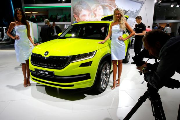 Models pose next to the Skoda Kodiak 4 X 4 at the Paris Motor Show in Paris, France (AP Photo/Michel Euler)