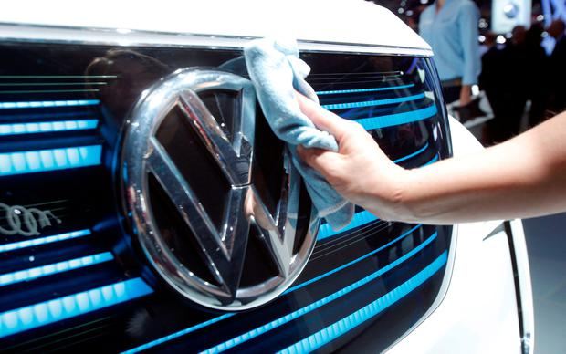 A worker shines the grill of a new Volkswagen electric car during a press conference at the Paris Motor Show in Paris, France (AP Photo/Michel Euler)