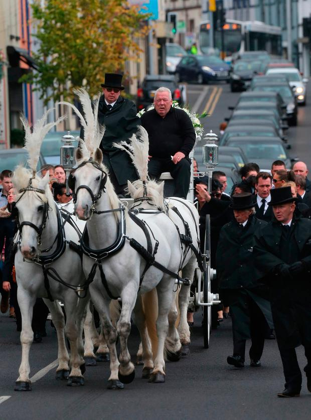 Owen Crumlish (top right), the widow of mother-of-11 Violet Crumlish, dubbed the Queen of the Travellers, sits on a horse drawn hearse during her funeral at St Peter's Church in Lurgan, County Armagh. Niall Carson/PA Wire