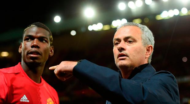 Manchester United's Portuguese manager Jose Mourinho (R) gestures to Manchester United's French midfielder Paul Pogba as he arrives on the pitch