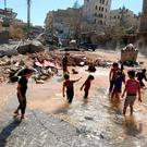 Children play with water from a burst water pipe at a site hit yesterday by an air strike in Aleppo's rebel-controlled al-Mashad neighbourhood, Syria