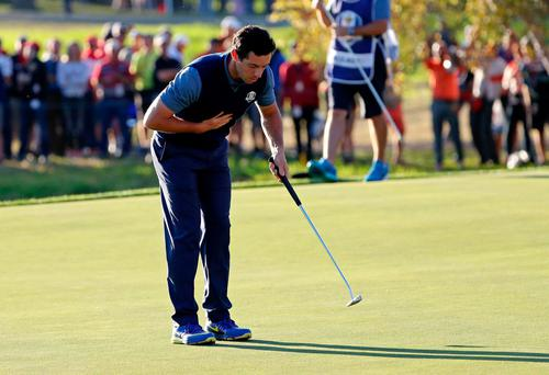 Rory McIlroy sarcastically bows to a muted American crowd after he holed the final putt to win his match. Photo: USA TODAY Sports