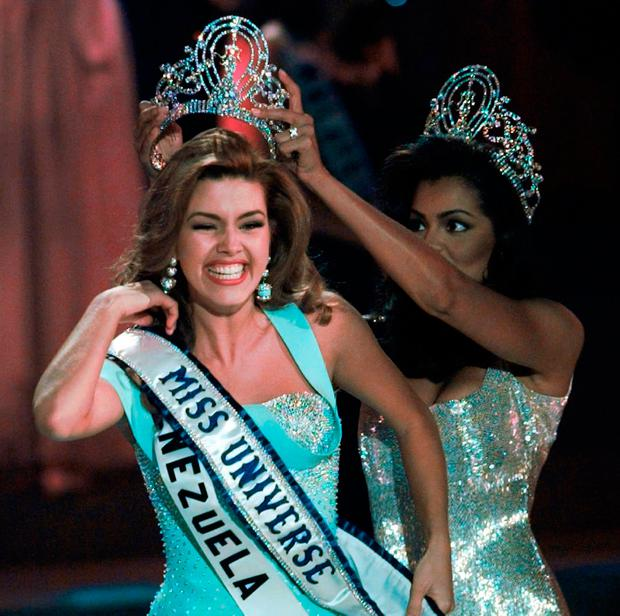 FILE - In this May 17, 1996, file photo, the new Miss Universe Alicia Machado of Venezuela reacts as she is crowned by the 1995 winner Chelsi Smith at the Miss Universe competition in Las Vegas