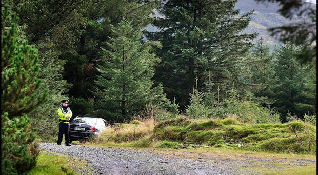 A Garda preserves the scene where the mans body was discovered off the Ballinascorney Road in Brittas. Pic Steve Humphreys
