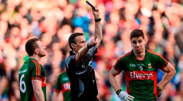 Lee Keegan of Mayo, right, is shown a black card by referee Maurice Deegan