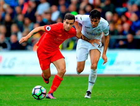 Liverpool's Philippe Coutinho tussles with Swansea's Jack Cork in the Reds' 2-1 victory at the Liberty Stadium yesterday. Photo: Nigel French/PA Wire.