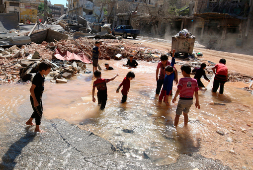 Playing in the battleground: Children splash in the water from a burst water pipe at a site hit by an air strike in Aleppo's rebel-controlled al-Mashad neighbourhood. Photo: Abdalrhman Ismail/Reuters