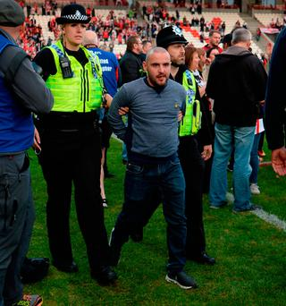A man is led away by police officers after Salford Red Devils late victory during the First Utility Super League, Million Pound Game at Craven Park, Hull