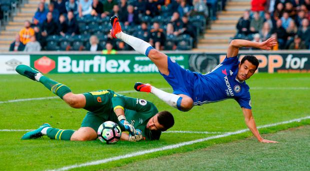 Chelsea's Pedro jumps over Hull City goalkeeper David Marshall. Photo credit: Danny Lawson/PA Wire