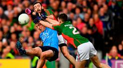 Cormac Costello kicks Dublin's final point of the game under pressure from Kevin McLoughlin (left) and Brendan Harrison in last year's All-Ireland final replay. Photo: Brendan Moran/Sportsfile