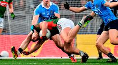 Mayo's Aidan O'Shea falls to the ground under pressure from Dublin duo Phily McMahon and Mick Fitzsimons. Photo: Paul Mohan/Sportsfile