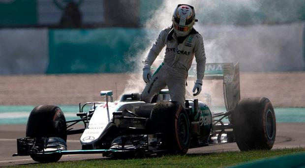 Mercedes driver Lewis Hamilton gets out of his burning car after an engine failure ruined his Grand Prix in Malaysia. Photo: Brian Ching/AP Photo