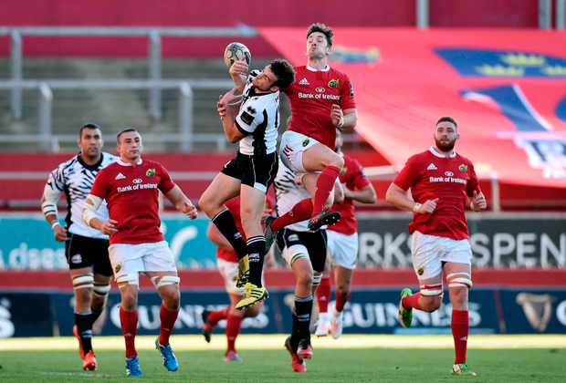 Munster's Darren Sweetnam jumps with Zebre's Edoardo Padovani on Thomond Park on Saturday. Photo by Diarmuid Greene/Sportsfile