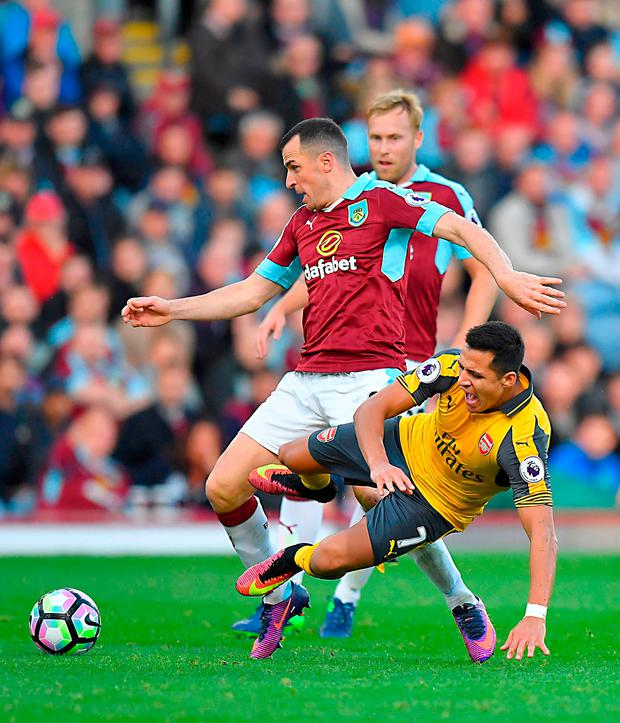 Burnley's Dean Marney (left) and Arsenal's Alexis Sanchez battle for the ball. Photo credit: Dave Howarth/PA Wire