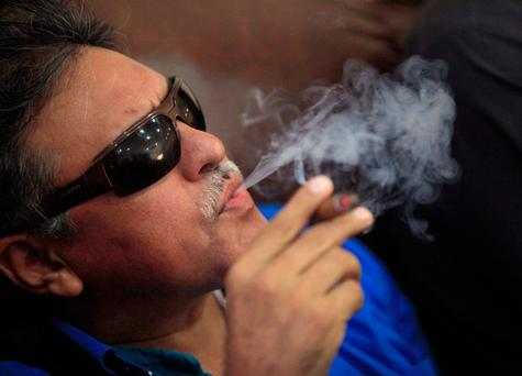 Revolutionary Armed Forces of Colombia (FARC) negotiator Jesus Santrich smokes a Cohiba cigar while watching a live transmission of the referendum on a peace deal, in Havana, Cuba October 2, 2016