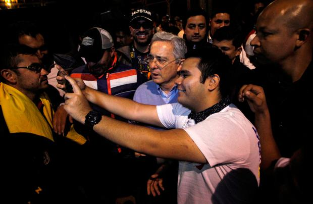 Colombia's former President Alvaro Uribe is photographed by a follower during a press conference after the nation voted