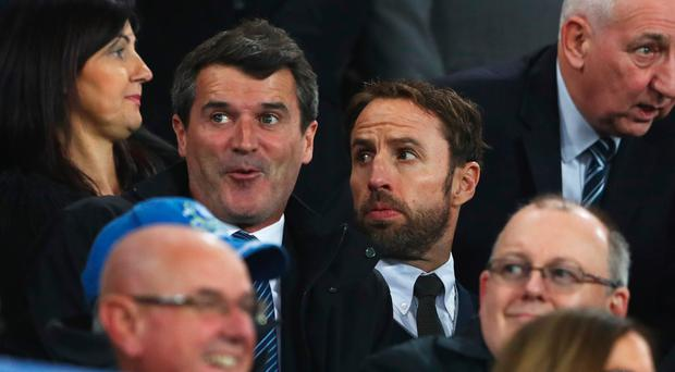 Gareth Southgate, caretaker manager of England (R), and Roy Keane look on from the stand prior to the Premier League match between Everton and Crystal Palace at Goodison Park