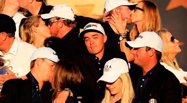 Rickie Fowler of the United States looks on as Kim Johnson, Zach Johnson, J.B. Holmes, Erica Holmes, Jimmy Walker, Erin Walker, Jordan Spieth, Annie Verret, Justine Reed and Patrick Reed celebrate with hugs and kisses Photo by Sam Greenwood/Getty Images
