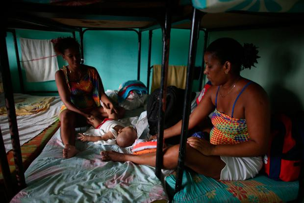 Jailene Albian, 18 (L), takes care of her six month old son together with her cousin Malbel Negrada, 41, in a shelter at the University of Guantanamo ahead of the arrival of Hurricane Matthew in Guantanamo, Cuba, October 3, 2016. REUTERS/Alexandre Meneghini