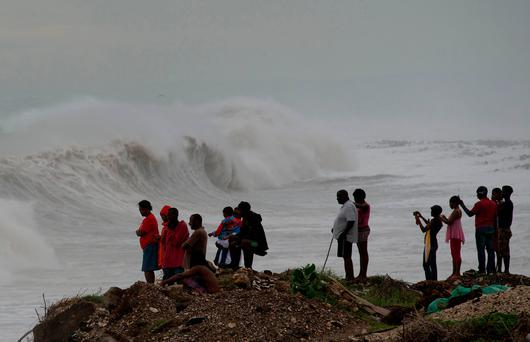 People stand on the coast watching the surf produced by Hurricane Matthew, on the outskirts of Kingston, Jamaica, Monday, Oct. 3, 2016. (AP Photo/Eduardo Verdugo)