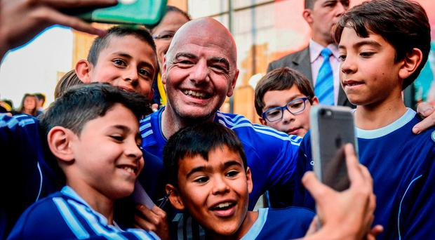 FIFA's President Gianni Infantino takes selfies during a friendly football match with former Colombian players and international football stars in Bogota