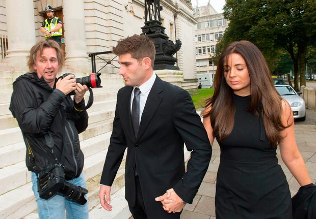 Chesterfield F.C football player Ched Evans (Centre) arrives at Cardiff Crown Court with partner Natasha Massey to stand trial for rape on October 4, 2016 in Cardiff, Wales