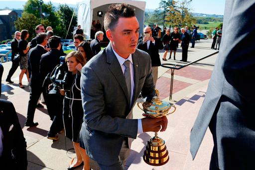 Golfer Rickie Fowler carries the Ryder Cup Trophy as he arrives for a memorial service for golfer Arnold Palmer in the Basilica at St. Vincent's College in Latrobe, Pa., Tuesday, Oct. 4, 2016. (AP Photo/Gene J. Puskar)