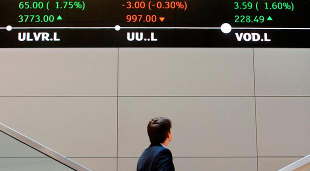 A man looks up at electronic ticker tape showing the FTSE 100 (in green) inside the London Stock Exchange. Photo: PA