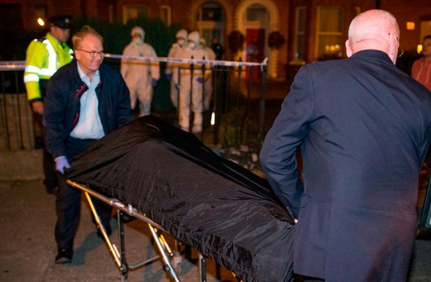 The victim's remains are removed from the house. Picture: Arthur Carron
