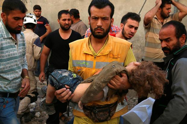 A medic holds a dead child after airstrikes in the rebel held Karam Houmid neighbourhood in Aleppo, Syria. Photo: Reuters